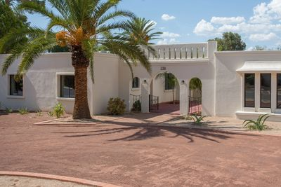 White mediterranean house with curved driveway.  U of A furnished rental in Tucson.