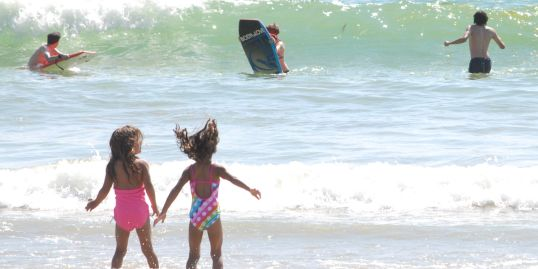 Two young girls watch teens using boogie boards in the ocean.