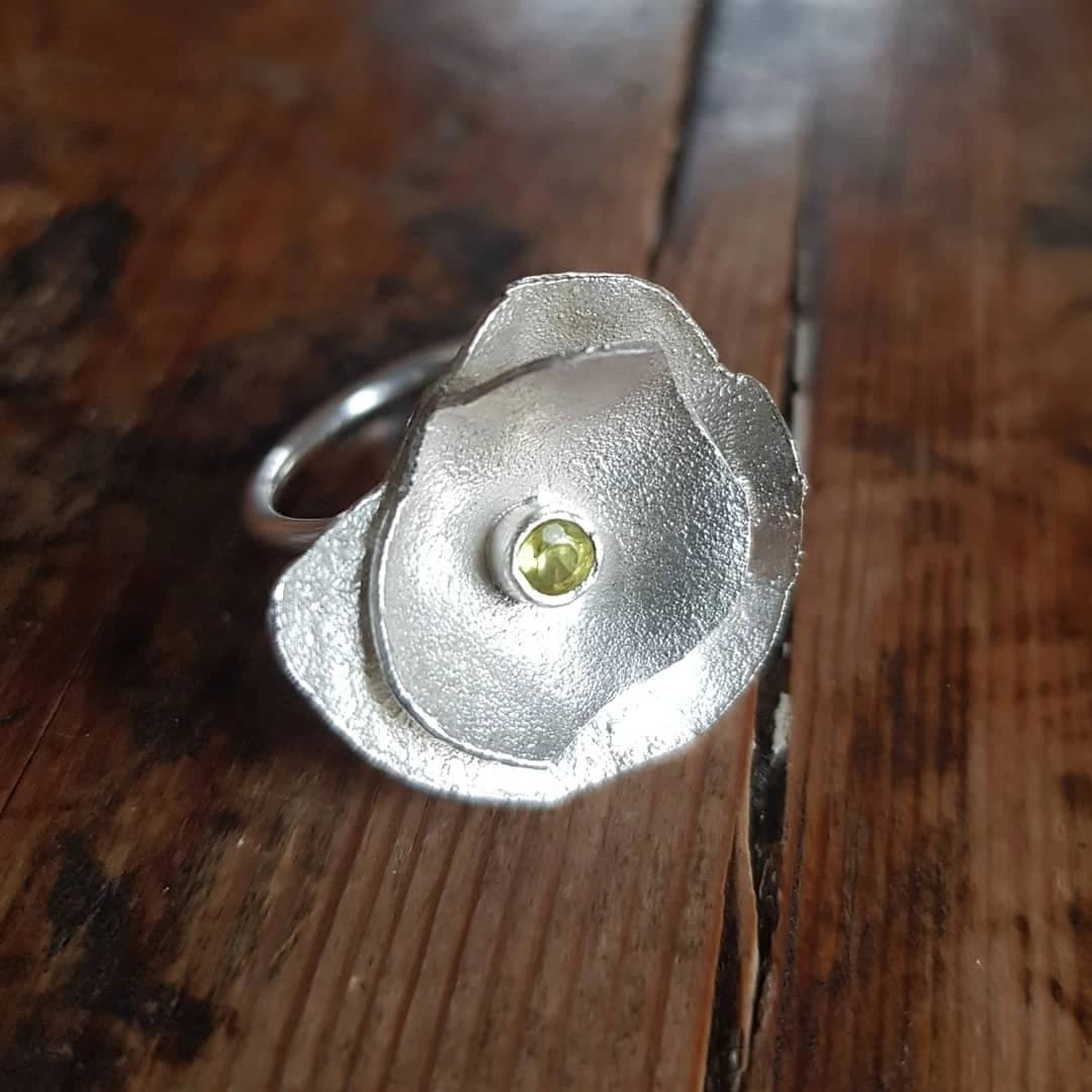 Reticulated silver abstract modern flower ring with an acid yellow sapphire detail.