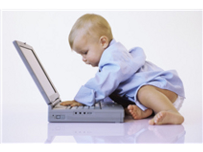 Toddler typing on a laptop computer.