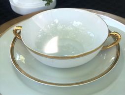 white saucer and soup bowl with gold handles.
