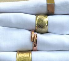 gold and copper napkin rings on white cloth napkins