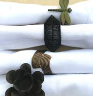 metal napkin rings in various shapes, on white cloth napkins