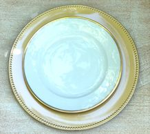 gold rimmed white plate on a painted gold charger.