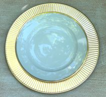 gold rimmed white plate on shiny gold charger