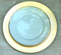 White plate with gold rim on gold foil charger