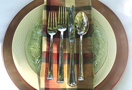 silver flatware on a plaid napkin and fall themed place setting.