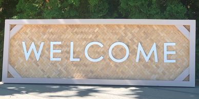 Welcome sign, white lettering over a woven cane background.