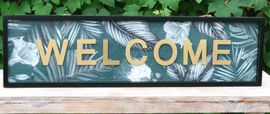 welcome sign in gold on a green background