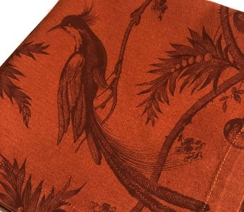 rust cloth napkin with bird motif