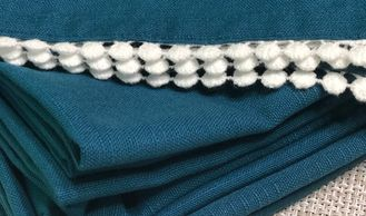 teal cloth napkin with white pom trim