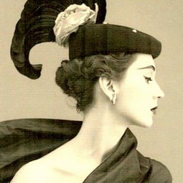 Elegant Fashionable Female Model in Silk with a Haute Couture Hat with Ribbon, Feathers and Pearls Vintage 1920.