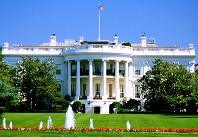 The White House in Spring Washington D.C. with Flowers in Bloom and Fountains on a Sunny Day with Very Green Grass, awaiting handcrafted Made in the U.S.A. Crafts, Raffia and Ribbons on Holiday display.