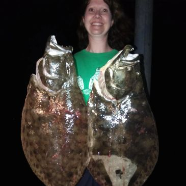 A lady in a green shirt, happy, smiling, holding two gigantic Flounder that she gigged