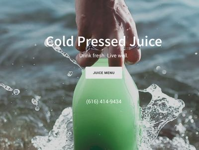 Website design image of a hand holding a bottle of juice in the lake with water splashing around it.