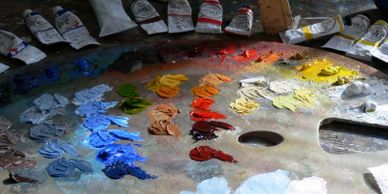 Tubes of oil paint and bright colours of red, yellow and blue on the artist's large, curved palette