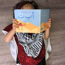 Palestinian child reading an Arabic children's book