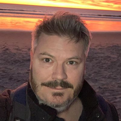 Color photograph of Aaron at the beach at sunset
