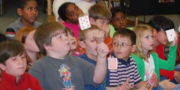 Kids playing with cards, one boy flipped card in the air.
