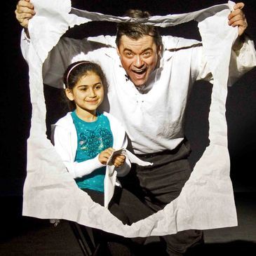 Young girl with magician John Tudor, looking thru paper circle.