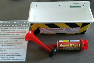 Emergency signal pack including air horn, container and personalised emergency evacuation sign