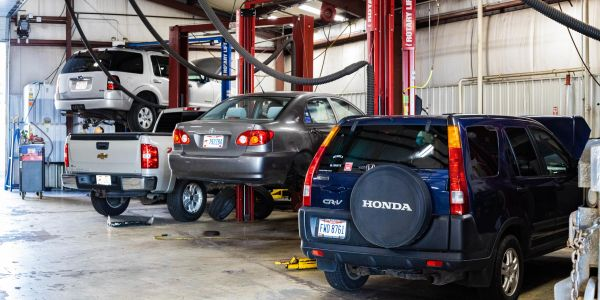 SUV, Truck, Car and other automobiles on shop lifts being worked on.