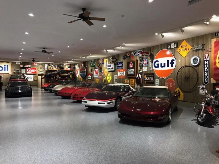 Large garage with a newly epoxy-coated floor, 10 plus sports cars and signage on the walls.