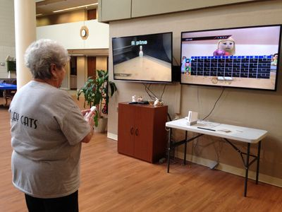 Senior citizen playing Wii Bowling at Weston Senior Center
