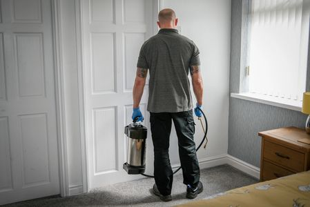 Pest control technician applying an ant treatment in a house.