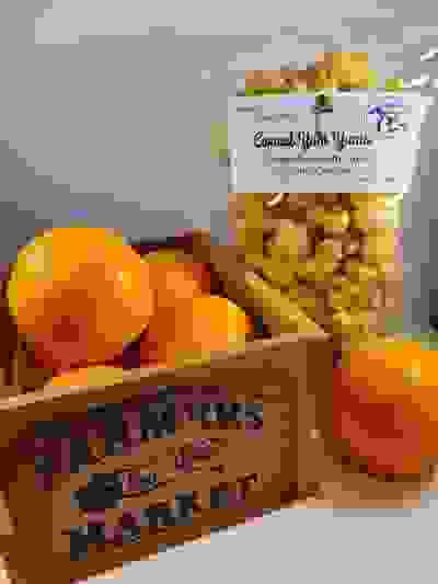 "The flavor of the month Candied Oranges placed behind a small crate filled with Oranges with ""Farmer"