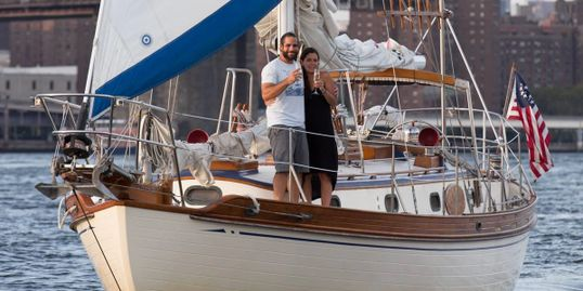 2 people drinking champagne on a sailboat