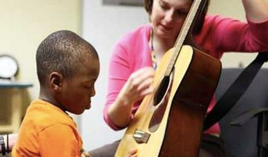child playing guitar with autism