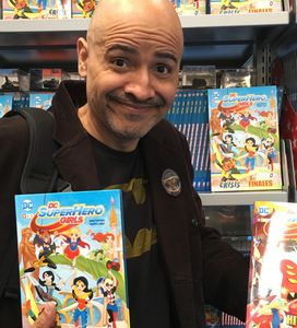Yancey posing with DC Super Hero books