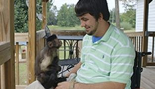 Bradley sits in wheelchair outside on his porch with Jerri his Monkey Helper on his lap facing him