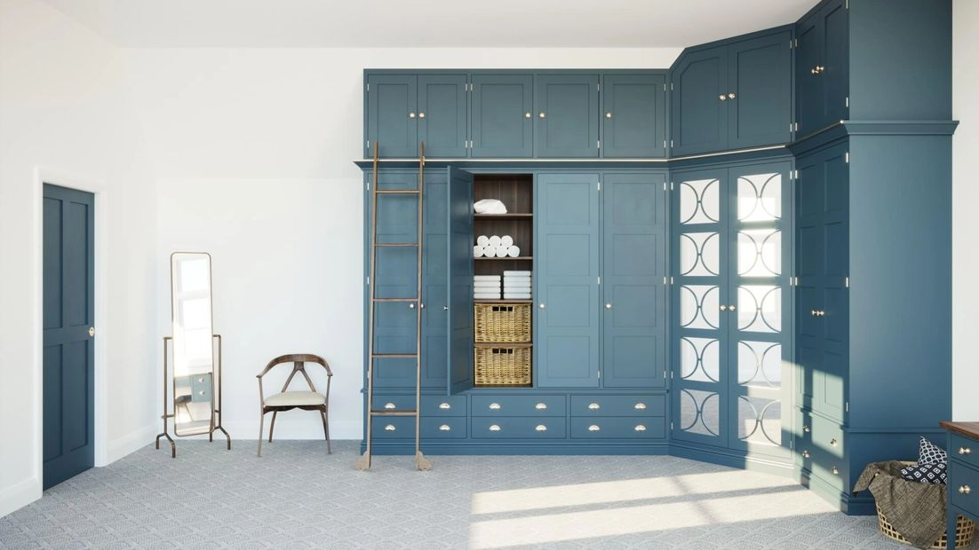Farrow & Ball 'Hague Blue' wardrobes with mirrored doors and brushed brass handles