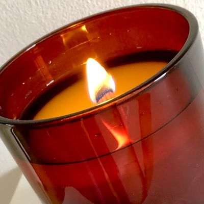 A soy candle burning with a ribbon wick.