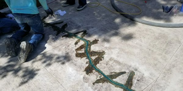 Concrete crack repair on a driveway prior to overcoating