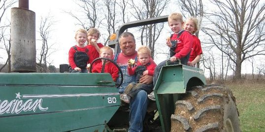 Buster and some of his grandkids sitting with him on the tractor enjoying tasty Woolf Farms apples.