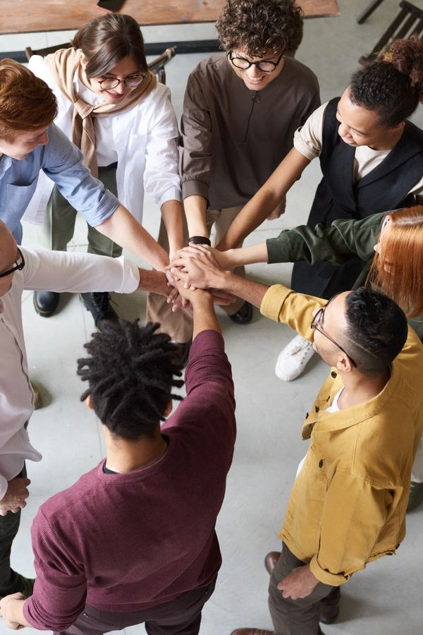 People in a circle gather hands in the middle