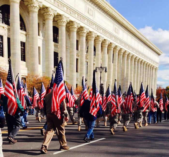 veterans marching the streets as part of a parade holding american flags