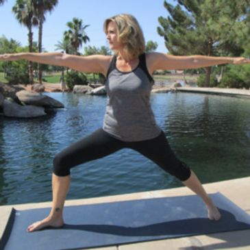 Renee Johnson, yoga instructor performing warrior 2 position in Freestone Park in Gilbert AZ