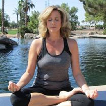 Renee Johnson, yoga instructor sitting Lotus position in Freestone Park in Gilbert AZ