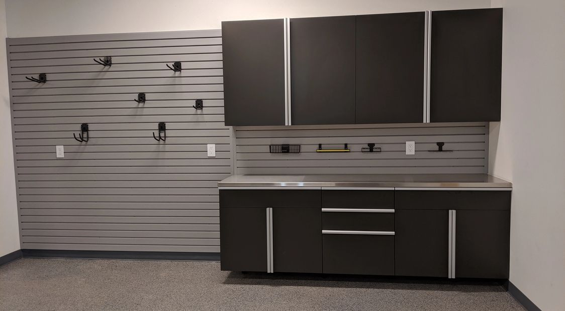 Slate Garage Cabinets with Extruded Steel Handles, a stainless steel countertop, and slatwall.