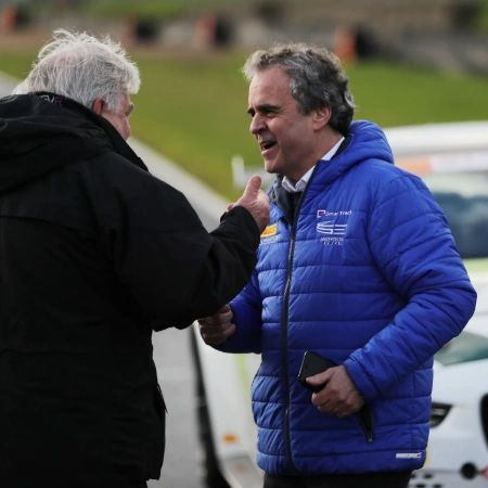 Team Principal Graeme Glew wearing his blue Series Elite coat discussing race tactics