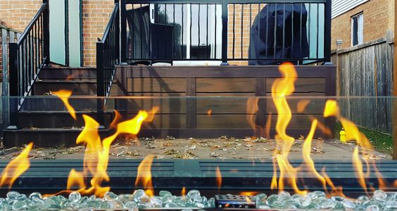 A nice photo of a fire pit on Trex deck built in Burlington,On.  The deck includes aluminum railing