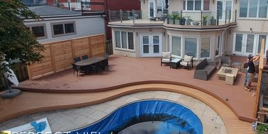 Custom curved Deck built in Toronto on lake Ontario. Includes roof decking, custom glass railing.