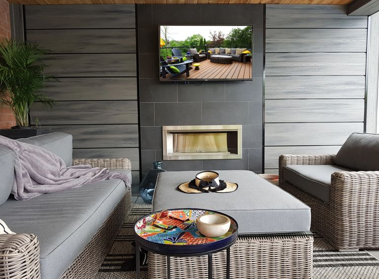 Feature outdoor fireplace wall underneath a Trex  deck in Oakville.  Landscaping was designed by us.