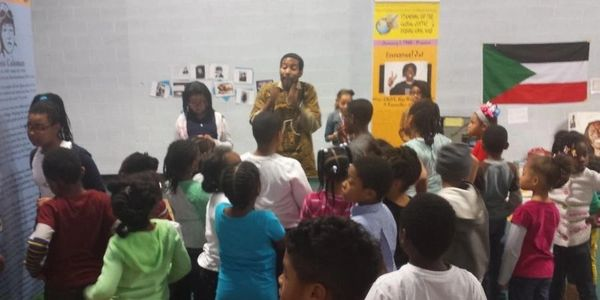 Dr. Ayize with the children at the Children's Interactive History workshop
