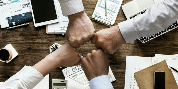 A business team fist-bumping, represent our dedicated team of representatives that help you find the insurance coverage you need.