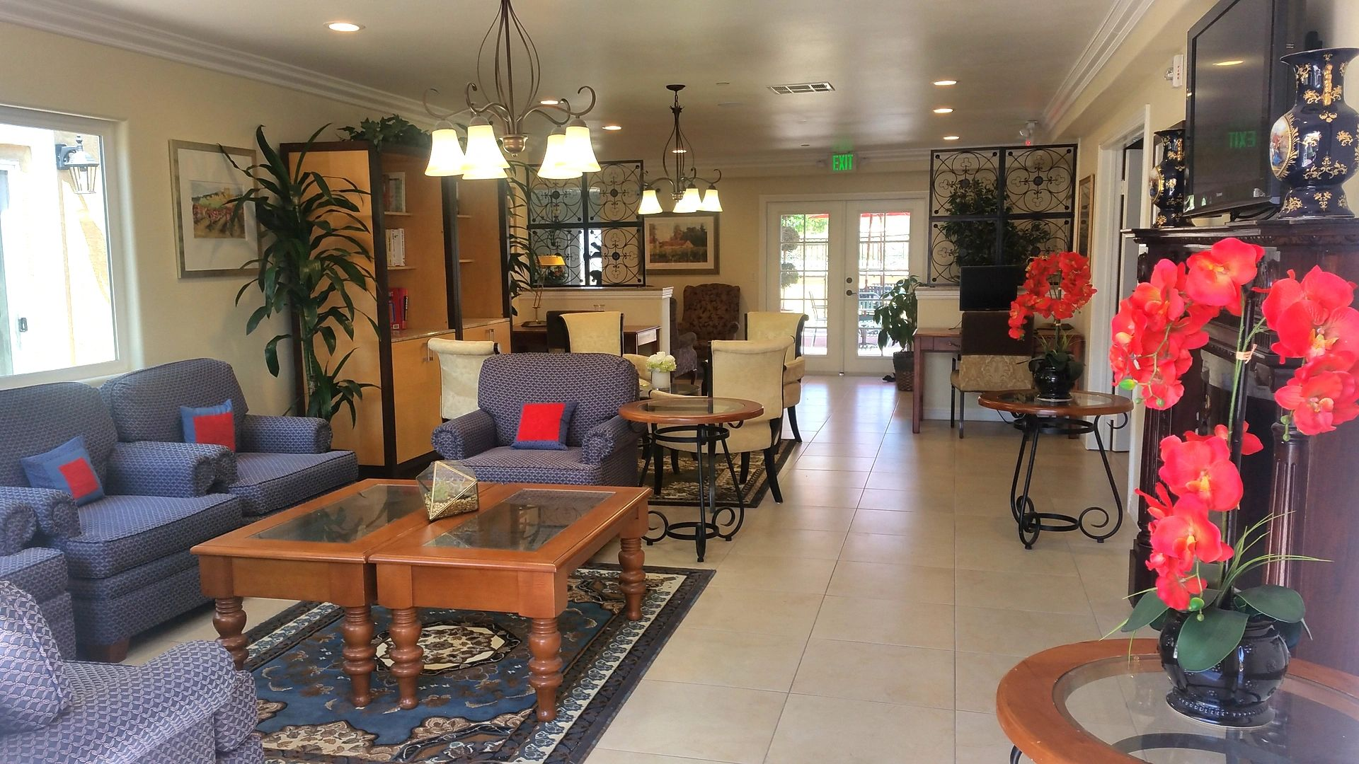 The living area of this assisted living facility features several blue and white chairs, red flowers, and more.